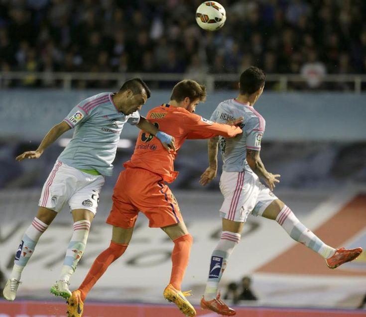 El defensa del FC Barcelona Gerard Piqué salta por el balón con el defensa argentino Gustavo Cabral y el chileno Pedro Pablo Hernández  del Celta de Vigo.