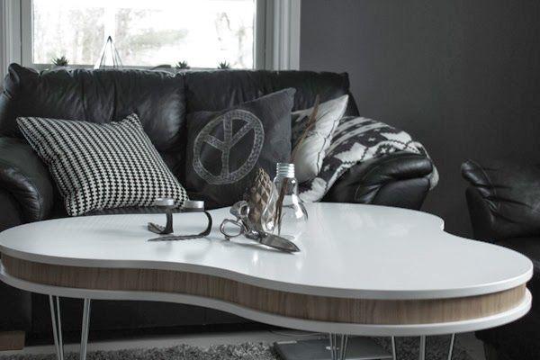 svart och vit kudde från ikea, vitt soffbord treklöver, peacetecken på kudde, glödlampa i inredningen, grå matta i vardagsrummet, svart soffa, gråa väggar, vardagsrum inspiration