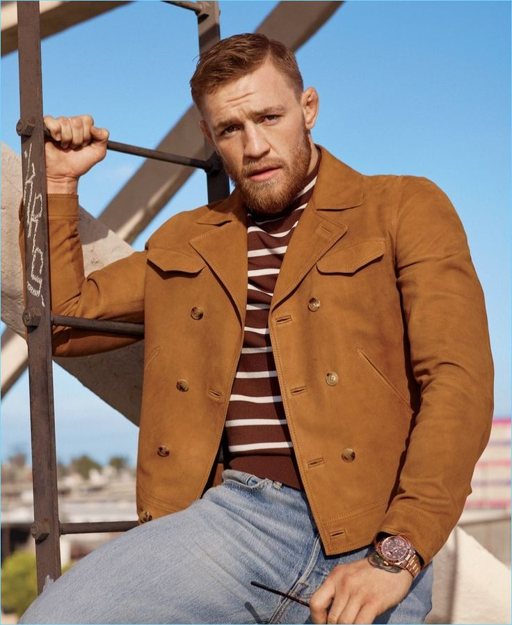 Appearing in a photo shoot for GQ Style, Conor McGregor dons a Boglioli suede jacket with a Neil Barrett t-shirt. McGregor also wears Levi's jeans and a Rolex watch.