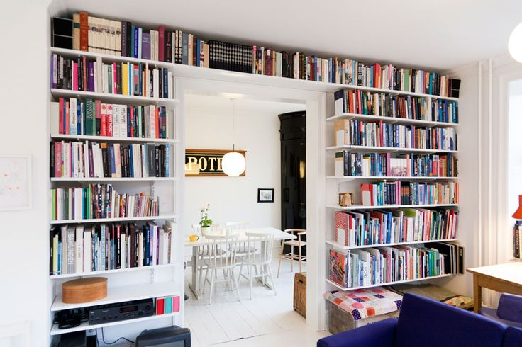 Wall of books. Loving the blue sofa.