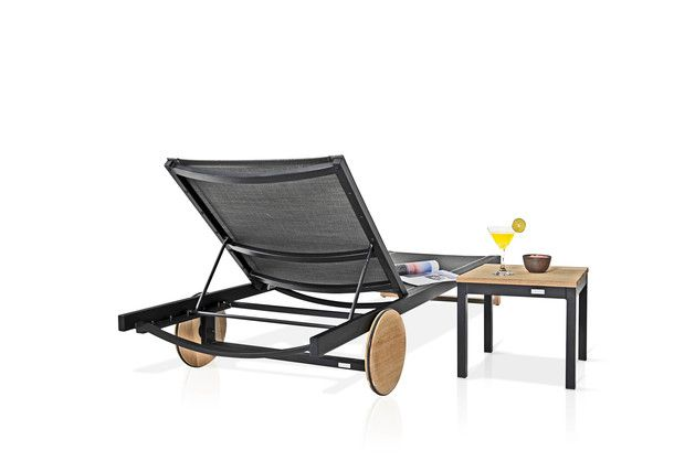 """Ecca Chaise lounge w teak finish on wheels that cleverly conceal the hardware. Clean, modern design and use of materials that naturally add an element of warmth. Perfect piece for poolside lounging. Available in multiple colors, this sleek and handsome lounger will effortlessly elevate your outdoor living. Overall: 27.5""""W X 78.5""""D X 11""""H Weight: 31.4 lbs. Material(s): teak, aluminum, batyline"""