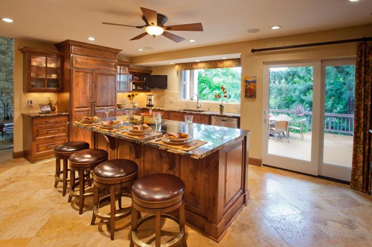 The warm tones and finishes in this craftsman style kitchen create a welcoming design. A wood door refrigerator and freezer blend beautifully into the cabinetry. A long island is perfect for in-kitchen eating on the leather barstools with nailhead trim finish. Light, neutral marble floor tile and light walls keep the room bright.