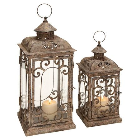 "Set of two distressed metal candle lanterns with scrollwork overlay and glass panels. Product: Small and large lanternConstruction Material: Metal and glassColor: Weathered brownAccommodates: (1) Candle each - not includedDimensions: Small: 15"" H x 7"" W x 7"" DLarge: 20"" H x 9"" W x 9"" DNote: Not recommended for outdoor useCleaning and Care: Wipe with a dry cloth"