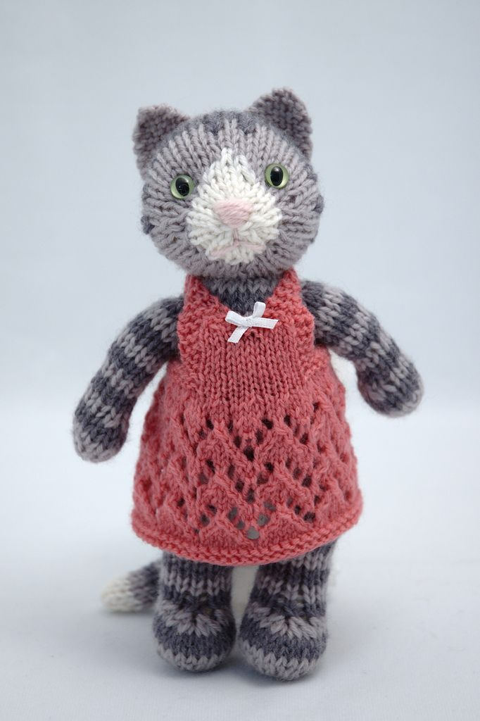Thanks for all the interest in this pretty kitty!  Unfortunately, this toy was one-of-a-kind made as a custom order, so there is no pattern. However, you could make a similar toy by modifying my Siamese Kitty pattern (www.ravelry.com/patterns/library/siamese-kitty). Work the legs, arms, body, and tail in 2-row stripes of light and dark grey. The back of the head is all dark grey (until about row 15), then it changes to light grey for the face. I made the white nose starting on Row 19. On…