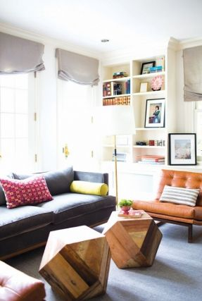 Eclectic sitting area with colorful built in shelves, leather chair and geometric coffee tables