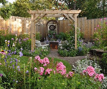Now full of a wide array of perennials, garden room is connected to  side yard by a winding gravel pathway. Tall fences offer privacy from neighbors, and profusely blooming flowers attract butterflies. It has become a favorite spot to curl up with a book or magazine and plan next garden project.
