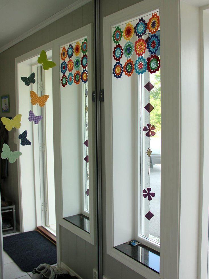 Pequeña cortina, a modo de bandó, sobre barra. Aplicaciones multicolores de ganchillo.:
