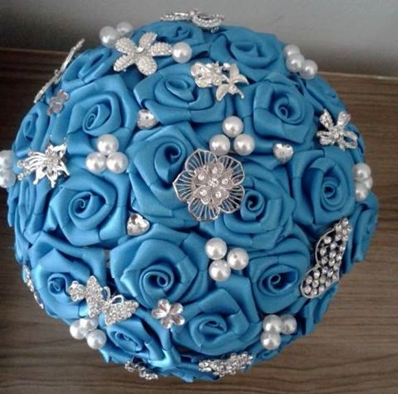 Buquê de flores azul turqueza em cetim com broches prateados e acabamento em strass no cabo.    Os buquês são personalizados e montados de acordo com o gosto da noiva.     Eles são únicos sendo que nunca existirá um buque idêntico ao outro.  Composto de broches em tons de prata cravejados em strass, flores de cetim e pérolas.  No cabo do buquê: cetim e broche (É feito de acordo com o gosto da noiva ou noivo)    Significado da cor azul - simboliza confiança e tranqüilidade.  Usar algo em azul…