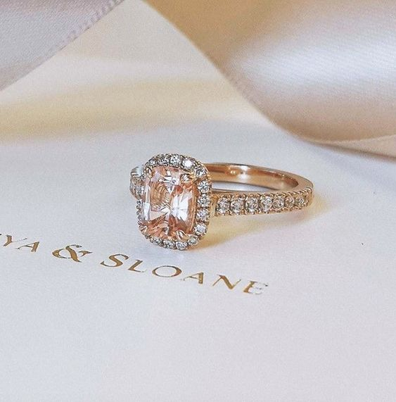 Naveya & Sloane bespoke cushion cut peach sapphire, with a claw set diamond band and halo. Crafted in 18k rose gold.
