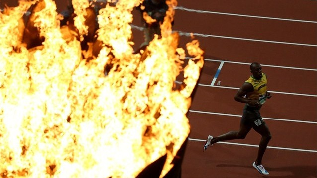 Usain Bolt of Jamaica runs past the Olympic torch after crossing the finish line to win the Men's 100m Final