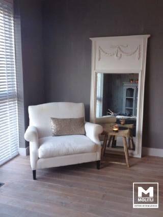mooie houten vloer - grijze wand - witte fauteuil - shutters - spiegel voor ruimtelijk effect