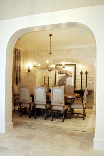 """I like the cozy, """"wine cellar"""" feel of the stone walls and soft lighting in this dining room."""