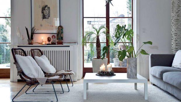 Skamler af rustikt træ står side om side med et stramt designet hvidt spisebord i køkken-alrummet. Og grangrene med røde julehjerter lyser op mellem de moderne møbler. Kontrasterne er tydelige hjemme hos Pernille Dybkjær – alligevel virker indretningen gennemført raffineret og rolig.