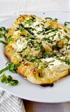 Lemon Ricotta White Pizza   A summery recipe made with garlic and olive oil, ricotta, parmesan, mozarella cheese, on fresh naan, then, once crisped in the oven, garnished with fresh basil and lemon zest.