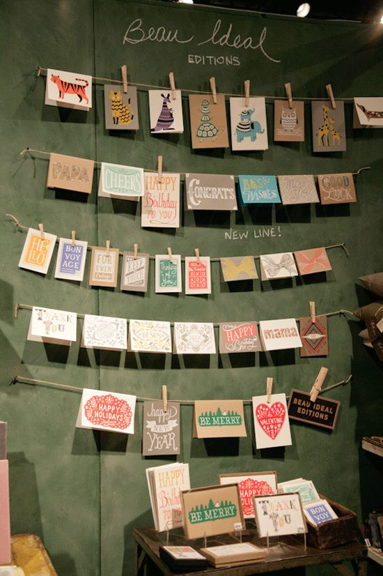 cards on clothes line | i like this idea in a store. 1) number the rows with decals 2) have numbered drawers below for people to take a wrapped one. 3) Also solves my pet peeve of people unwrapping greeting cards!