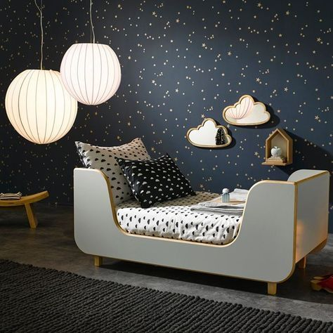 night sky inspired kids room with gold star walls, lanterns, cloud wall hangings, and modern monochromatic bedding