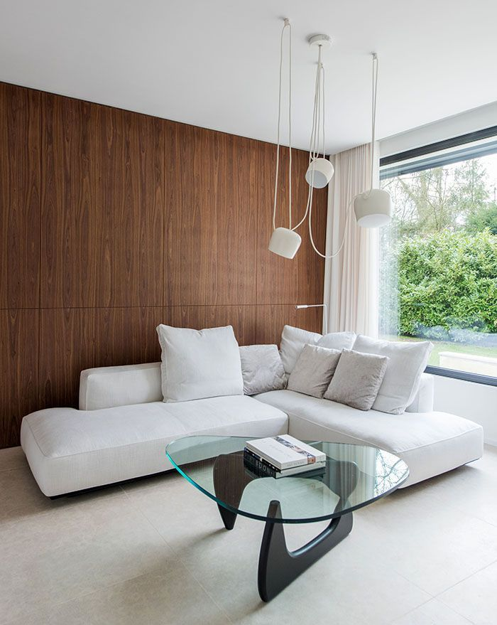 This spacious living room setting features a unique glass table, expansive white couch, a wood wall and white AIM pendant lights by Ronan and Erwan Bouroullec.