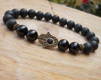 Schutz Hamsa Armband. Dieser Edelstein Hamsa Armband ist mit 8 mm Tiger Eye und schöne Kambaba Jaspis Perlen entworfen. Es ist aufgereiht in festen elastischen Faden, leicht an-und ausziehen.  Die Hamsa ist ein alten nahöstlichen Amulett symbolisiert die Hand Gottes. In allen Religionen ist es ein schützendes Schild. Das Wort Hamsa bedeutet 5 und bezieht sich auf die fünf Finger. Die Zahl 5 ist eine leistungsstarke Reihe und symbolisiert Verteidigung, macht und Reichtum. Auch steht Segen und…