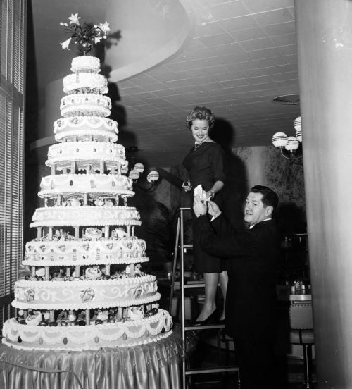 Mona Freeman, actress, cuts the 10-foot tier cake... | Yesterday's Print