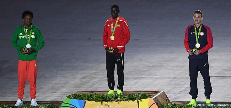 (L-R) Silver medalist Feyisa Lilesa of Ethiopia, gold medalist Eliud Kipchoge of Kenya and bronze medalist Galen Rupp celebrate on the podium at the medal ceremony for the men's marathon at the Closing Ceremony of the Rio 2016 Olympic Games at Maracana Stadium on Aug. 21, 2016 in Rio de Janeiro.