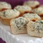Baked Spinach Dip Mini Bread Bowls  13.3 oz roll of refrigerated french bread loaf, I used Simply Pillsbury  2 Tbsp extra virgin olive oil  2 c baby spinach, coarsely chopped  1 clove fresh garlic, minced  3 oz softened cream cheese  1/2 c light sour cream  2 Tbsp fresh shredded parmesan cheese  1/8 tsp McCormick Gourmet Ancho Chile Pepper  1/8 tsp McCormick Gourmet Garlic Salt  1/8 tsp McCormick Gourmet Sicilian Sea Salt  1/8 tsp freshly ground black pepper  1/3 c shredded mozzarella cheese