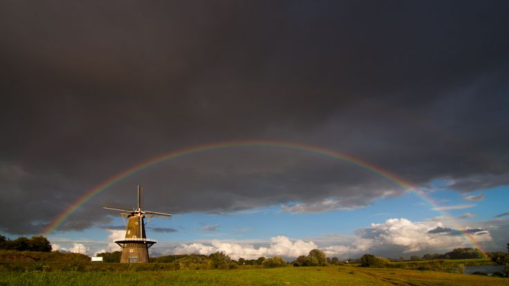 Korenmolen De Hoop in Gorinchem is trapped within a double arched rainbow. Not sure where the pot with gold will be, but the mill will continue to grind the golden wheat.
