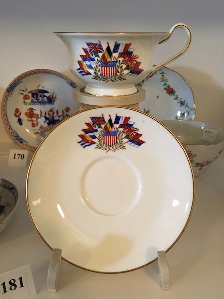 This cup & saucer is part of a set produced by Wedgwood during World War I at the behest of philanthropist Lillian Gary Taylor to raise money for Allied charities and the war effort. The sets were sold to a select group of private customers, including President Woodrow Wilson and King George V. From left to right, the flags represent Cuba, Romania, Montenegro, Italy, Great Britain, Belgium, France, Russia, Japan, Portugal, and Serbia. The United States is represented by the shield in the…