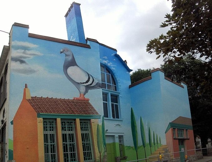 """Paul De Gobert - Le grand pigeon Sur les murs d'une des plus vieilles écoles communales du vieux quartier Saint-Job à Uccle, Réalisée par Paul De Gobert il y a une trentaine d'années vient d'être restaurée fin 2007 par l'artiste lui-même. """"Le grand pigeon"""" est la star de l'oeuvre. Il a été choisi par P. De Gobert pour rappeler que la colombophilie fût une des passions principales des habitants de ce quartier Saint-Job à Uccle. Rue Jean Benaets - Uccle - Bruxelles"""