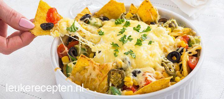 mexicaanse nachos met veel kaas Ingrediënten  150 gr tortilla chips 3 eetlepels olijven in ringetjes 100 gr cherrytomaatjes 125 gr zure room 1 avocado 75 gr gerapste kaas 2 eetlepels mais uit blik eventueel jalapenopepers voor de liefhebber
