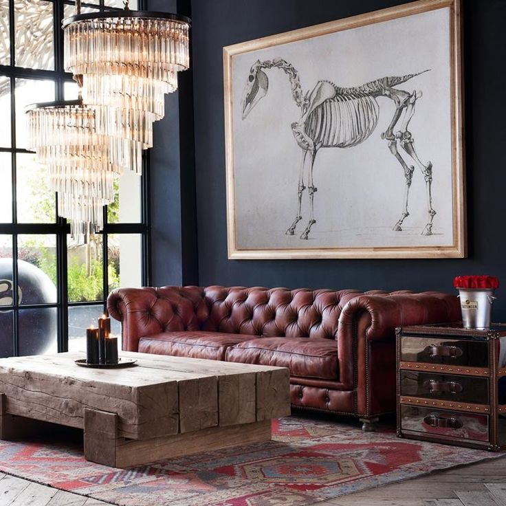 Leather sofa, chunky wood coffee table,  oriental rug, large chandelier and oversized art work, a well designed living room.