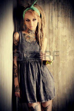 tattoo girl: Chica rubia sexual con rastas fascinantes posando junto a la pared del grunge. Pin-up de estilo.
