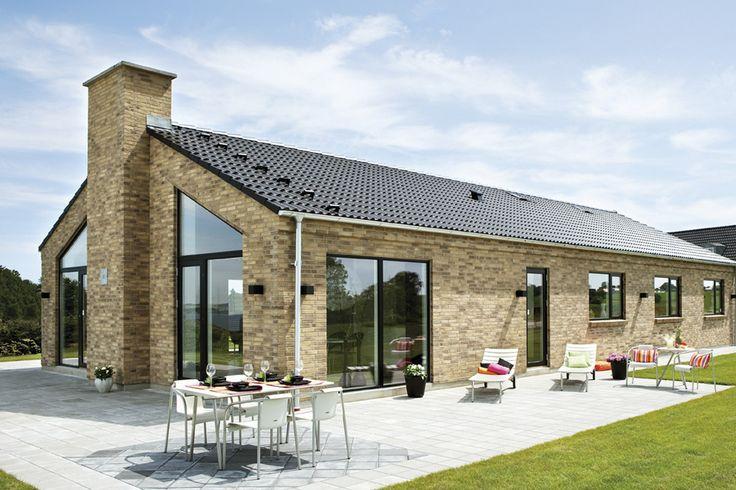 Smukt længehus med murede gesimser, sorte betontagsten og sorte træ/alu vinduer