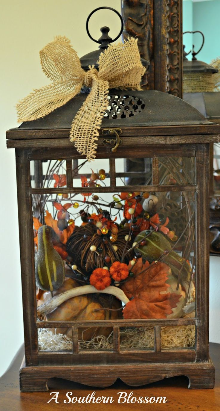 Pumpkins, gourds, twigs and berries in a lantern for fall.