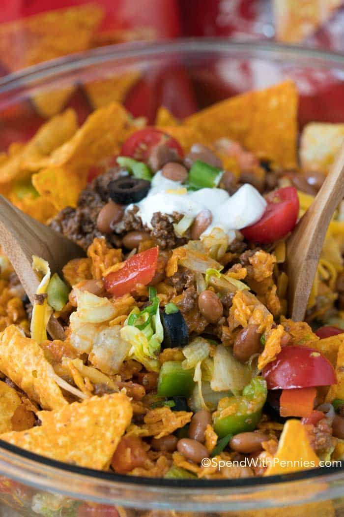 Everyone at our potluck went CRAZY for this Dorito Taco Salad!  Loads of seasoned ground beef, veggies, beans and Doritos in a zesty sauce!