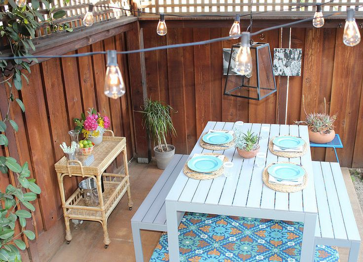 Create an affordable outdoor dining space with Ikea's picnic table and benches and vibrant outdoor rugs from Cost Plus World Market