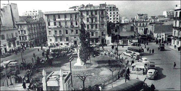 Η Πλατεία Κάνιγγος, το 1954, πριν από τη διχοτόμησή της. Στη φωτογραφία βλέπουμε την οδό Κάνιγγος 15-17. Το κτήριο στη διασταύρωση των οδών Κάνιγγος 19 και Χαλκοκονδύλη 1 καταστράφηκε στα Δεκεμβριανά του 1944. Πιθανόν και το κτήριο από την απέναντι γωνιά να γκρεμίστηκε το ίδιο διάστημα. Φωτογραφία από το Αρχείο Αφων Μεγαλοκονόμου.