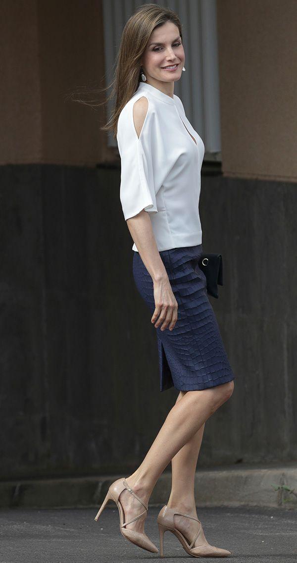 La Reina con blusa blanca de Adolfo Dominguez, falda azul de piel efecto cocodrilo de Hugo Boss, cartera azul marino, de Carolina Herrera; y sandalias de Magrit, de piel de serpiente en nude