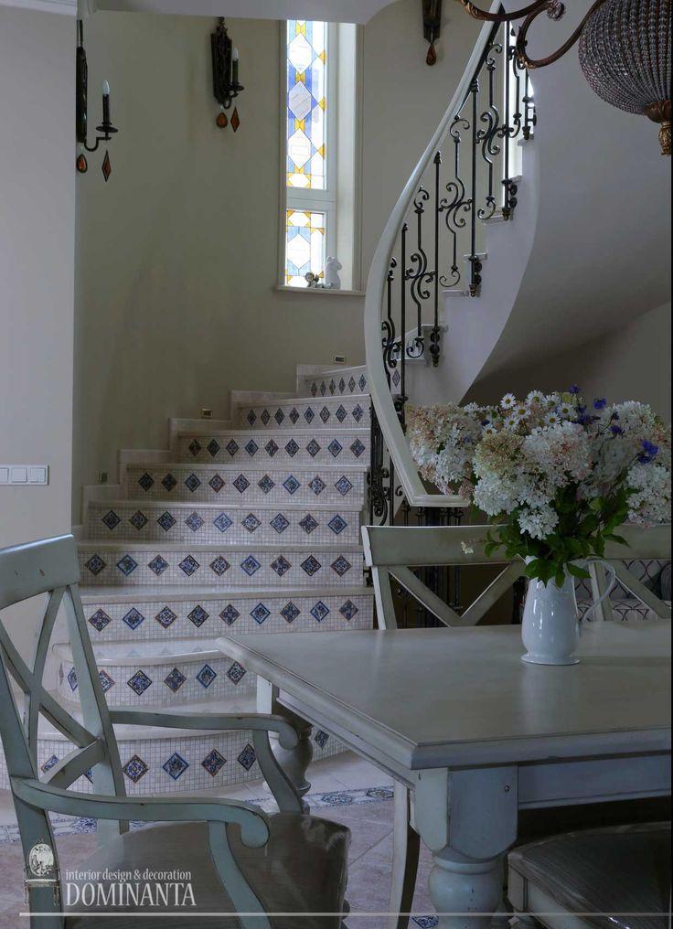 Проходная столовая с лестницей. Лестничный холл освещают витражи. Над обеденным столом – светильник в стиле бохо.