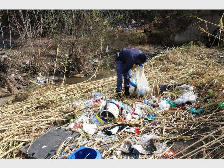 A participant in the clean-up operation clears the area of garbage.