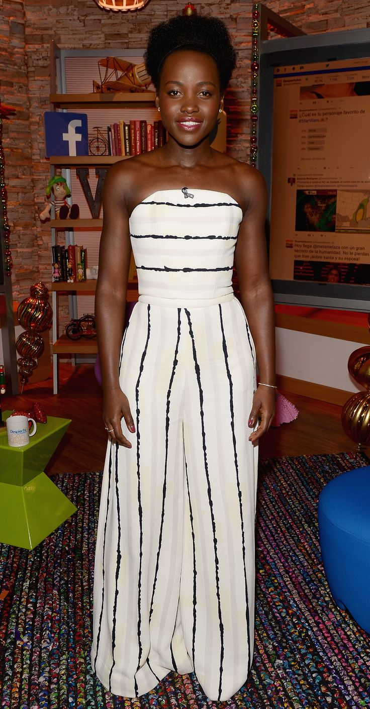 Lupita Nyong'o was snapped on the set of Despierta America to promote Star Wars: The Force Awakens in a sleek strapless striped white one-piece, complete with delicate gold jewelry.
