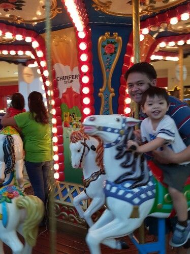Thrilled to see my husband equally happy with my son riding the carousel.
