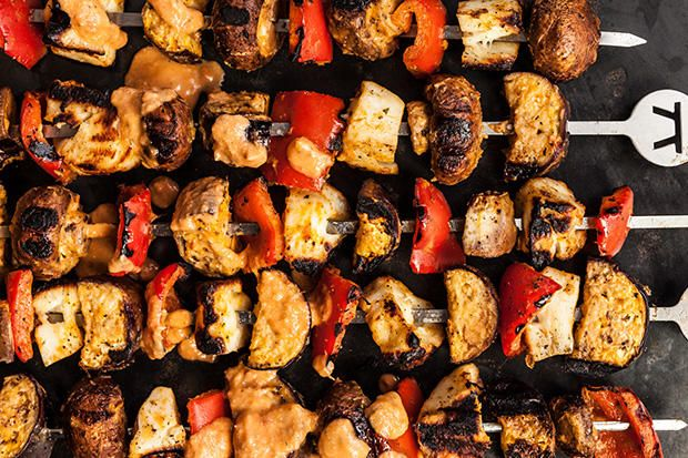 This recipe for grilled vegetarian skewers has halloumi cheese, bell peppers, mushrooms, and eggplant with a tomato-artichoke sauce.
