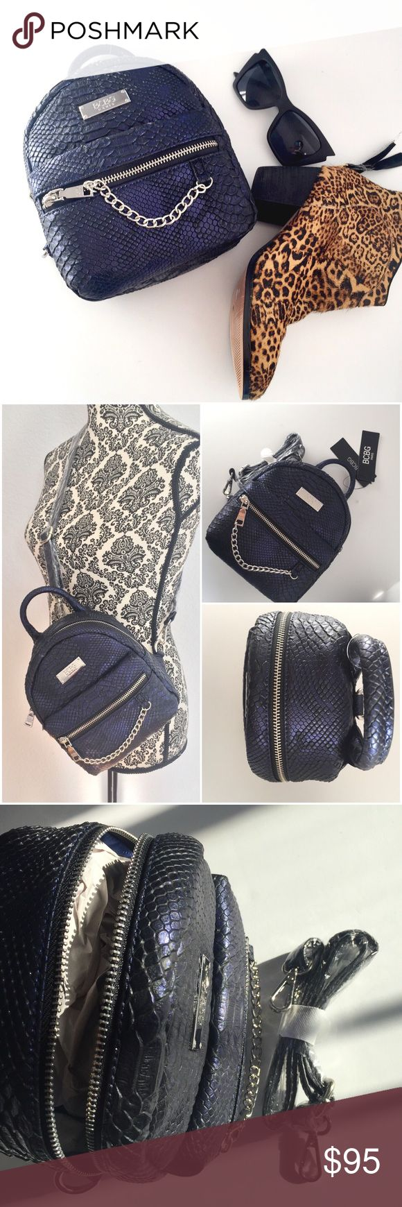 """BCBG Paris main st petite backpack NWT COLOR Blue. BCBG Paris Main St Petite backpack. Comes with adjustable and removable strap. Approx 9""""W 8""""H 4""""D 12""""L silver hardware. Color is amazing, it changes from blue to black and has a bit of shimmer. Faux snack skin. BCBG Bags"""