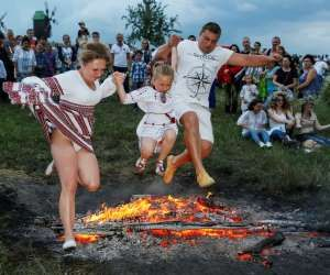 People jump over a campfire during a celebration on the traditional Ivana Kupala... - REUTERS/Gleb Garanich