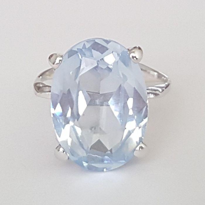 18 kt wit gouden ring met een blauwe spinel van 9 ct-grootte: 191 mm 20/60 (EU)  18 kt wit goud cocktail ring met een potentieel synthetische hemelsblauw spinel instellen in vier uitsteeksels op een mooi frame dat is openworked met cirkelvormige patronen.Materialen:18 kt (750/1000) witgoud geen zichtbare kenmerk. De stenen test voor 18 kt goud was positief.Een synthetisch spinel ovaal knippen met een mooie hemelsblauwe kleur 18 mm lang door 9 mm breed met 75 mm lang met een geschatte gewicht…