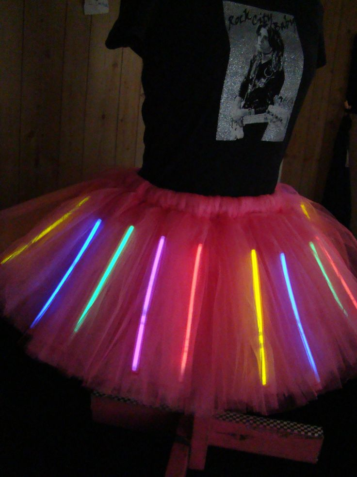Totally eighties, so funky, extremely easy! Thread neon glow bracelets through a poofy puffy tulle tutu skirt: http://www.flashingblinkylights.com/light-up-products/glow-bracelets.html