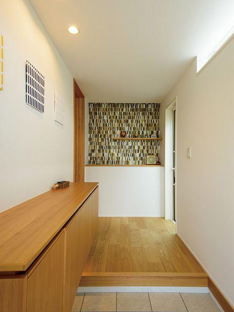 大容量のシュークロークのおかげで玄関もスッキリ。「自分の好きなものに囲まれて生活したい」と、雑貨や花、写真を飾っている。