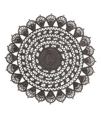 Et rundt, hullmønstret teppe i jute.