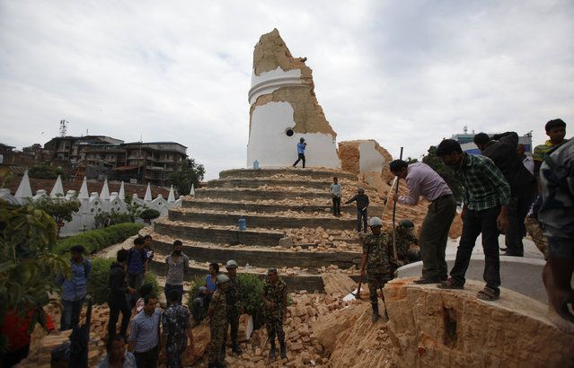 Volunteers work to remove debris at the historic Dharahara tower, a city landmark, after an earthquake in Kathmandu, Nepal, Saturday, April 25, 2015. (Photo by Niranjan Shrestha/AP Photo)