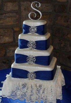 My first wedding cake.  Tier one is white cake with oreo cookie frosting, tier two is chocolate cake with raspberry filling, tier three is white cake with strawberry filling and tier 4 is strawberry cake with buttercream frosting.  Fondant covered and airbrushed with pearl.  Royal blue ribbon with rhinestone brooches.  Couldnt believe how heavy this cake was!!